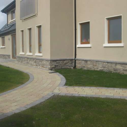 Rendered house with stone cladding around the base